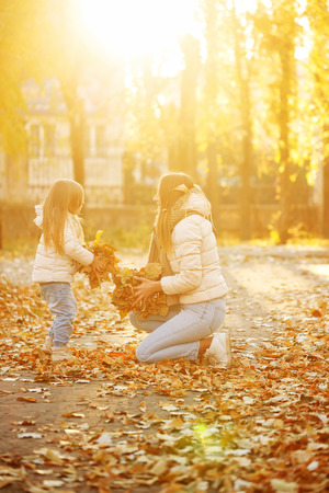 Family walk. Mother and daughter toss up fallen leaves. Autumn Park. Cute family relationships. Sunset. Warm toning.