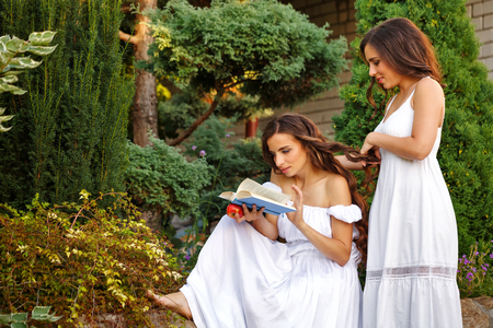 Two sisters. She reads a book, and her sister, her plait braids. Girls in long white dresses. Family time in the backyard. Stock Photo
