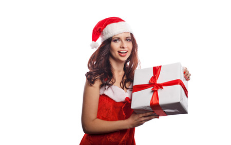 Young attractive girl in a suit of Santa Claus holds a Christmas gift. She is happy. Sale. Christmas mood. Stock Photo