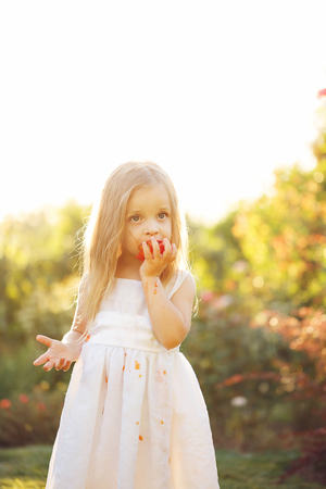 piddle: Nice little girl eating a tomato. She eats a vegetable. Girl soiled white dress in tomato juice. Sunset illuminates the flowing hair. Stock Photo