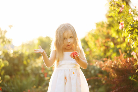 Nice little girl eating a tomato. Girl soiled white dress in tomato juice. Sunset illuminates the flowing hair.