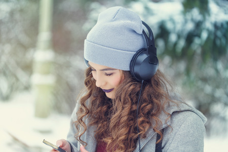 Portrait of pretty attractive girl hipster winter park. She is listening to music on headphones. Youth street fashion. Winter fun. Walks in the open air.