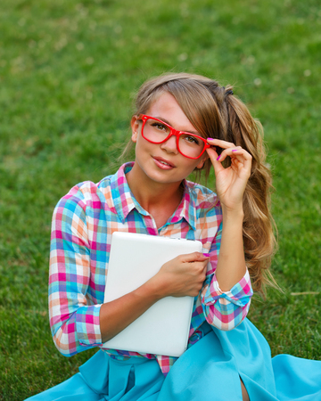 corrects: Lovely attractive girl with a laptop. She corrects glasses and sits on a green lawn in the park. A student takes a break from lessons. Shooting with a high angle.