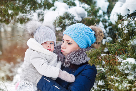 Mother and young daughter embracing in a winter park. Mother and daughter in her arms. Happy family. Childhood and parenthood happiness. Mother and daughter cheated her cheeks. Resentment. Stock Photo