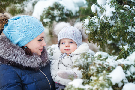 Mother and young daughter embracing in a winter park. Mother and daughter in her arms. Happy family. Childhood and parenthood happiness. Closeup portrait. Stock Photo