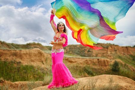 bailarinas arabes: Danza del vientre oriental de belleza. chica en el baile nacional vestido con el mantón al aire libre. Nómadas. Foto de archivo