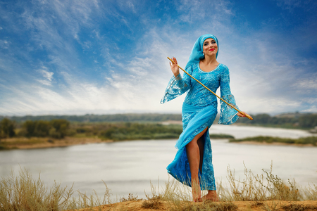 Oriental beauty Saidi dance. Nice girl in national dress dancing shepherdess with shepherds cane outdoors. Nomads. Stock Photo