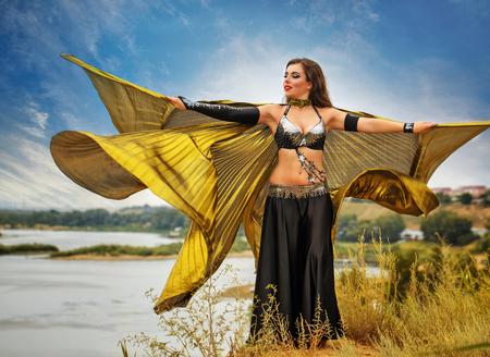 bailarinas arabes: Belleza oriental de baile con las alas. chica en el baile vestido nacional en el aire libre. Nómadas. Belleza y elegancia