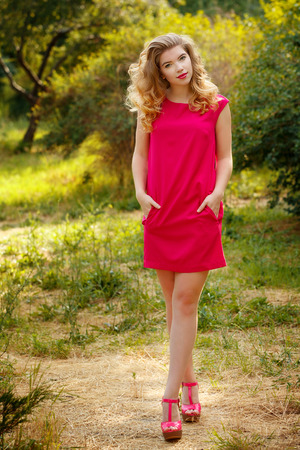 The girl in red dress with curly hair and walks in the park. Street fashion. Stock Photo