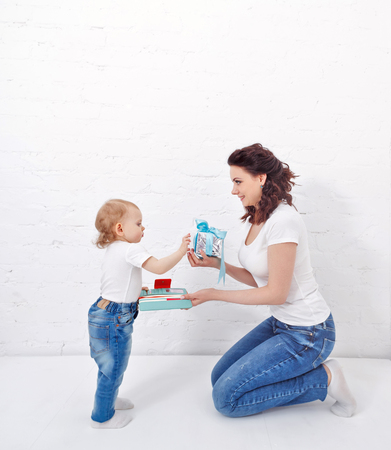 Mother and daughter are holding a purse and a gift. Mother and daughter dressed in jeans and white T-shirts. Family look.