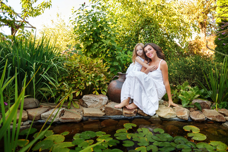 Two sisters in white dresses hug from jug pond with lilies. Family time.