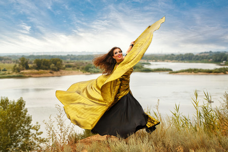 Oriental Beauty dance with wings. Nice girl in national dress dancing in the open air. Nomads. Firebird. Stock Photo