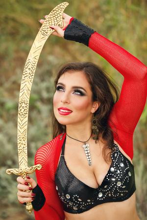 bailarinas arabes: Danza oriental de la belleza con una espada. Estilo tribal. Niña agradable en el baile nacional del vestido en el aire abierto. Nomads. Retrato Foto de archivo