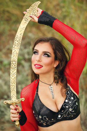Oriental Beauty dance with a sword. Tribal style. Nice girl in national dress dancing in the open air. Nomads. Portrait Stock Photo