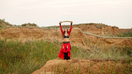 tribal dance: Passionate dance with a sword. Tribal style. Attractive girl in costume dancing outdoors. Sand dunes. Nomads. Oriental beauty