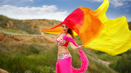 arabian harem: Oriental Beauty belly dancing. Nice girl in national dress dancing with shawl outdoors. Nomads.