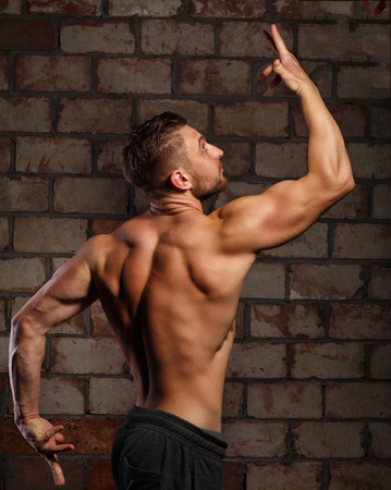 Man athlete posing at a brick wall. Bodybuilder ahead of the competition. Drying. Relief and sculptural body muscles. Healthy lifestyle concept.