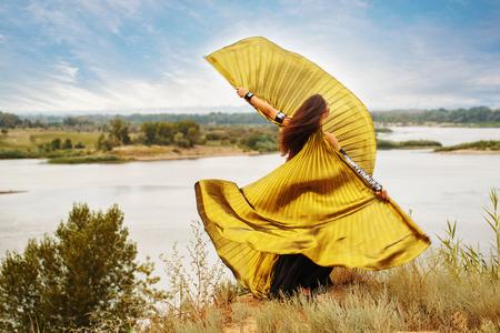 bailarinas arabes: Danza oriental de la belleza con las alas. Niña agradable en el baile nacional del vestido en el aire abierto. Nomads. Juego de oro.