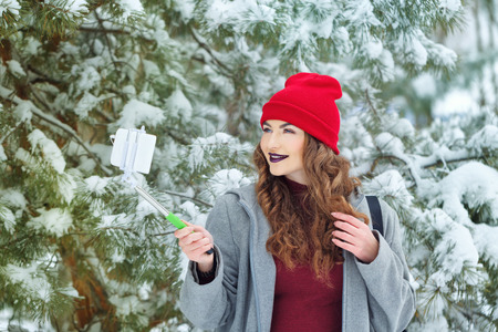 Portrait of pretty attractive girl hipster winter park. She makes selfie on a smartphone. Youth street fashion. Winter fun. Walks in the open air. Stock Photo