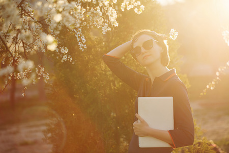 Cute girl holding a laptop in hand. Portrait against the setting sun and cherry blossoms. She straightens her hair in sunglasses Stock Photo