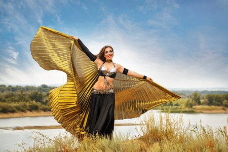 Oriental Beauty dance with wings. Nice girl in national dress dancing in the open air. Nomads. Beauty and grace. Stock Photo