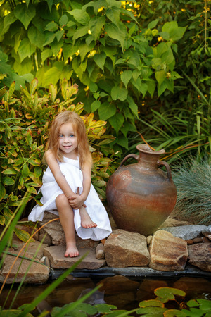 Nice little girl in white dress sitting by the pond with lilies. Old clay jug standing beside her.