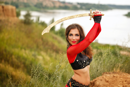 Oriental Beauty dance with a sword. Tribal style. Nice girl in national dress dancing in the open air. Nomads. A girl holding a sword Stock Photo
