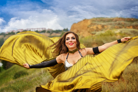 Oriental Beauty dance with wings. Nice girl in national dress dancing in the open air. Nomads. Grace.