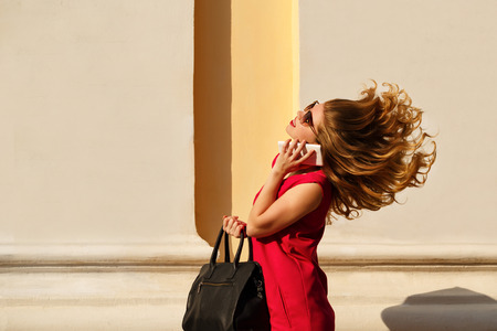 Girl in red dress, sunglasses, with curly hair and trendy handbag. Girl talking on the phone. Street fashion. Flying hair.