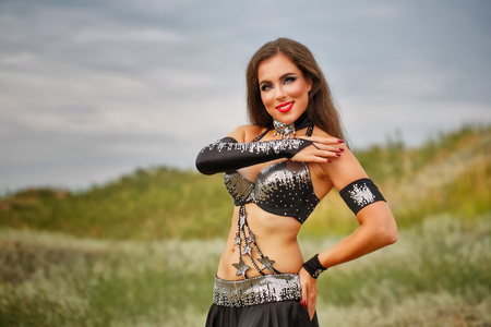 BELLY DANCING: Oriental Beauty belly dancing. Nice girl in national dress dancing in the open air. Nomads.