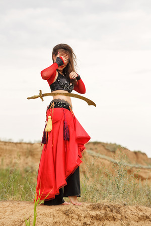 bailarinas arabes: Oriental Beauty dance with a sword. Tribal style. Lovely girl in costume dancing outdoors. Nomads. A sword is on the thigh of the girl.