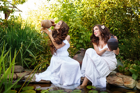 Two sisters in white gowns with pitchers pond with water lilies. One girl is drinking from an old crock.