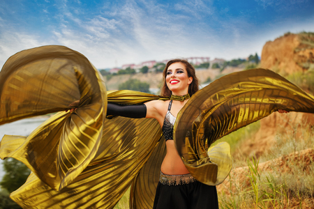 Oriental Beauty dance with wings. Nice girl in national dress dancing in the open air. Nomads. Sweep the wings.