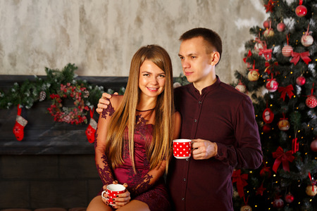Loving couple and Christmas. Man and woman drinking from mugs Hot Christmas drink. Cocoa with marshmallows. Stock Photo