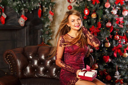 Lovely attractive girl holding a Christmas gift. The concept of a happy holiday.