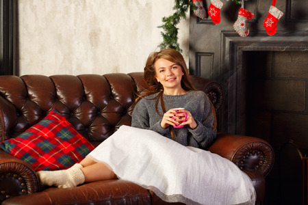 Cute attractive girl drinking hot Christmas drink cocoa with marshmallows. Shes on the couch. Warm Christmas evening. Stock Photo