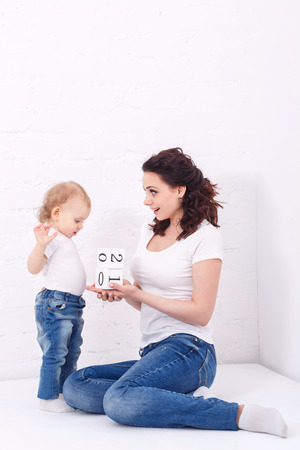 Mother and daughter playing with blocks. On dice have figures. Family education. Mother and daughter dressed in jeans and white T-shirts. Family look.