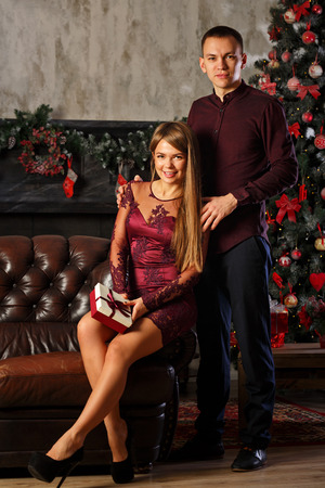 Loving couple and Christmas. Girlfriend gives her boyfriend a gift. Celebration for two. Family celebration.
