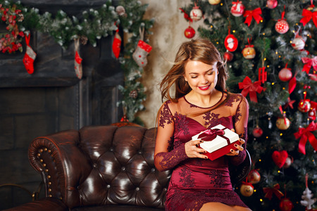 Sweet attractive girl holding a Christmas gift. The concept of a happy holiday.