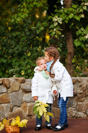 Two cute little sisters embracing in autumn park. Family time.