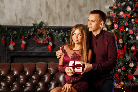 Loving couple and Christmas. He hugs his girlfriend and gives her a Christmas present. Stock Photo