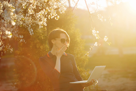 Cute girl student holding a laptop in hand. Portrait against the setting sun and cherry blossoms. The work is always with you. Warm toning. Shes in shock.