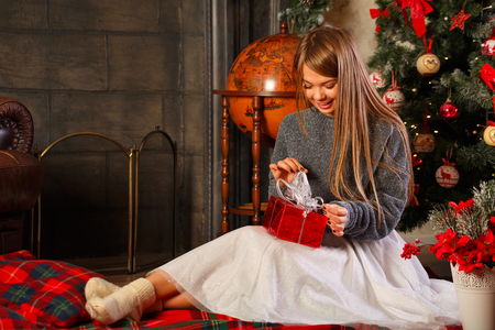 Sweetheart attractive woman unpacking a Christmas gift. Stock Photo