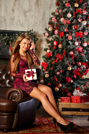 Cute attractive girl holding a Christmas gift. The concept of a happy holiday.