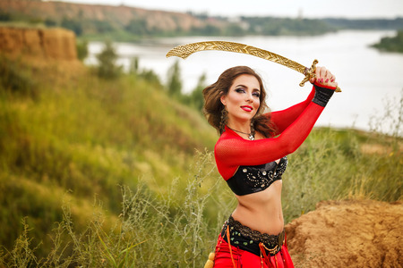 arabian harem: Oriental Beauty dance with a sword. Tribal style. Nice girl in national dress dancing in the open air. Nomads. Stock Photo