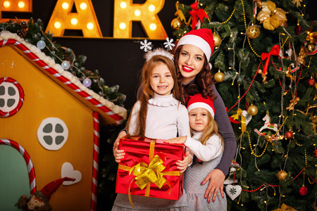eldest: Family is waiting for Christmas. Mother and two daughters in a Santa hat hugging near a Christmas tree. The eldest daughter is holding a Christmas present. Family celebration. Happy Motherhood and Childhood.
