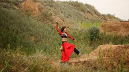 bailarinas arabes: Belleza oriental de baile con una espada. estilo tribal. encantadora chica en traje de mantener el equilibrio sobre un pie al aire libre. Dunas de arena. Nómadas.