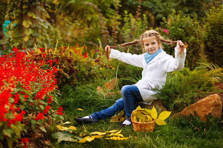 Cute little girl fooling around with her braids in the autumn park. Wicker basket standing beside her. Stock Photo