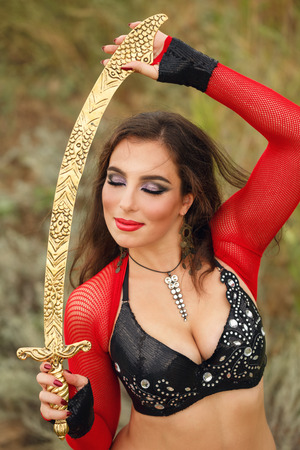 Oriental Beauty dance with a sword. Tribal style. Nice girl in national dress dancing in the open air. Nomads. Close-up portrait Stock Photo