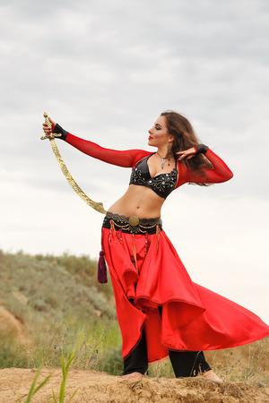 bailarinas arabes: Belleza oriental de baile con una espada. estilo tribal. encantadora chica en traje de baile al aire libre. Nómadas. Foto de archivo